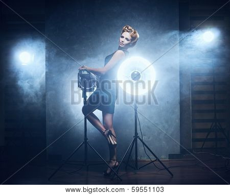 Young and emotional woman in fashion dress over glamour background (studio backstage)