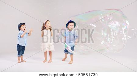 lovely little kids playing with soap bubbles