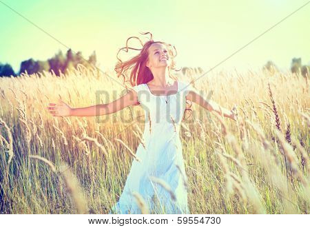 Beauty Girl Outdoors enjoying nature. Beautiful Teenage Model girl in white dress running on the Spring Field, Sun Light. Glow Sun. Free Happy Woman. Toned in warm colors.