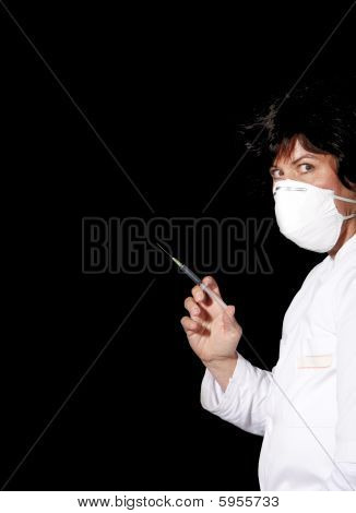 Female Doctor With Surgical Mask And Syringe Looking Spooky