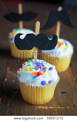 Cupcakes with black mustaches and colorful sprinkles