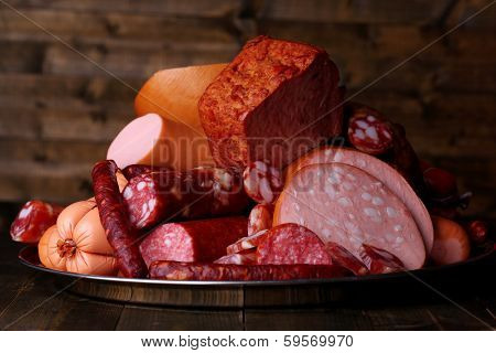 Lot of different sausages on salver on dark wooden background