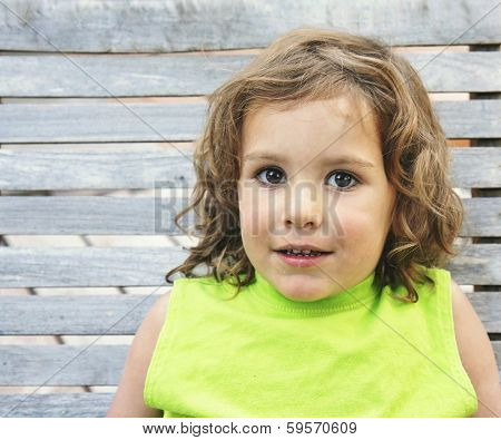a young girl sitting on a wooden bench close up