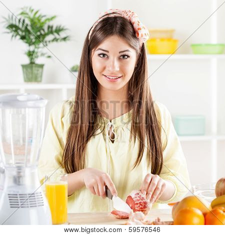 Young woman slicing Grapefruit