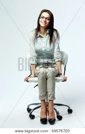 Young smiling businesswoman sitting on office chair on gray background