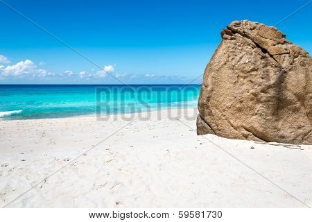 white sand beach with huge bolder