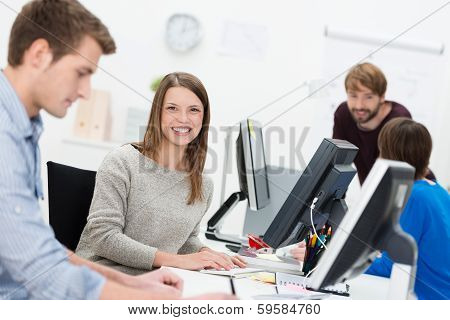 Smiling Young Businesswoman In A Busy Office