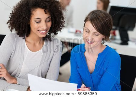 Two Smiling Businesswomen Working On A Document