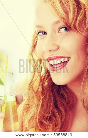 Young beautiful blond woman sipping cocktail (green ice tea)