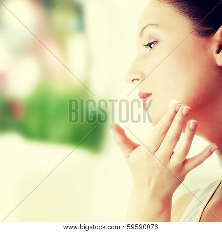 Woman applying moisturizer cream on face. Close-up fresh woman face.