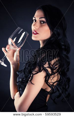 beautiful seductive woman with glass in hand