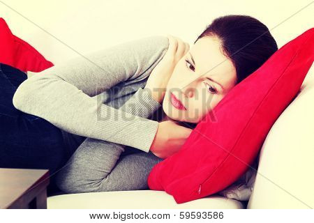 Front view portrait of a beautiful young worried woman lying on a sofa, hugging to a red pillow and holding her hands around her arms.