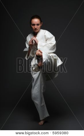 Girl In White Kimono Kicks Forward Left Leg