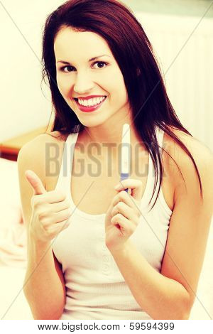 Front view portrait of a beautiful young smiling woman sitting on a bed, showing the pregnancy test and giving a thumb-up.