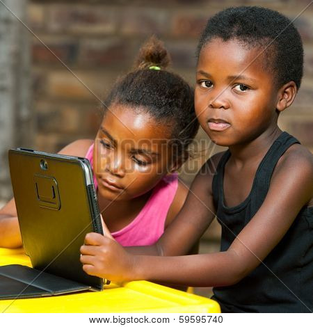 Two African Girls Sitting At Table With Tablet.
