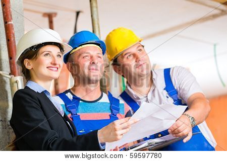 Construction site team or architect and builder or worker with helmets controlling or having discussion of plan or blueprint