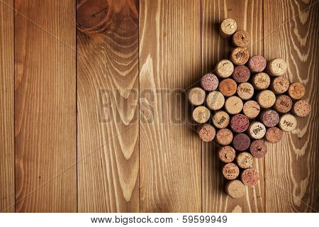 Grape shaped wine corks on wooden table background with copy space