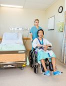 Full length of portrait of mature male patient sitting on wheelchair while nurse assisting him in ho