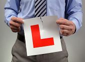 Businessman tearing up L plate concept for new business, apprenticeship or passing driving test