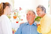 picture of hospice  - Happy elderly couple talking with their carer - JPG