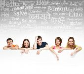 image of differences  - Group of teenagers over the background with the many words from the different languages  - JPG