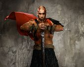 foto of legion  - Wounded gladiator with  sword covered in blood isolated on grey - JPG