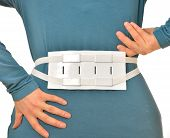 image of lumbar spinal stenosis  - woman wearing to back device for massaging of lumbar pain - JPG
