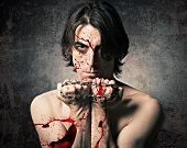 pic of torture  - Terrible evil man with an iron chain and covered in blood - JPG
