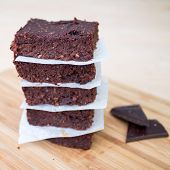 pic of chocolate fudge  - Fresh Homemade Vegan Chocolate Brownies stacked separated with parchment paper with two pieces of dark chocolate on the side on beige