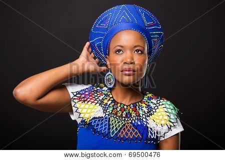 attractive south african woman in traditional attire looking up on black background