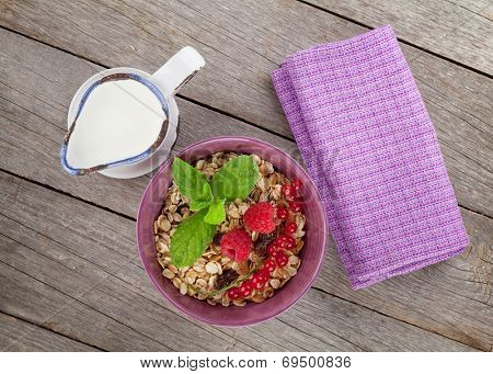 Healty breakfast with muesli, berries and milk. View from above on wooden table