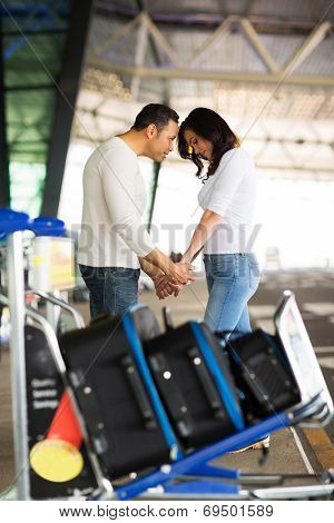 caring man comforting his girlfriend before boarding airplane at air port