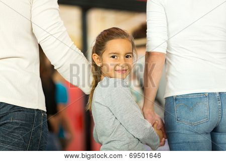 cute little girl holding her parent's hands and looking back at airport