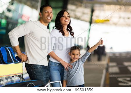 pretty young girl with parents in airport hailing taxi