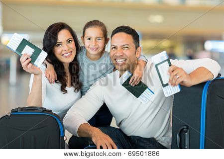happy family holding boarding pass and passport at airport