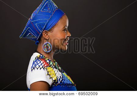 side view of young african zulu woman on black background