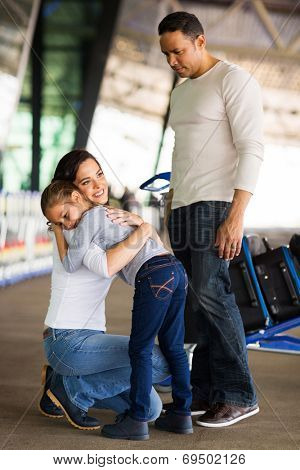 adult woman hugging her daughter at airport before departure