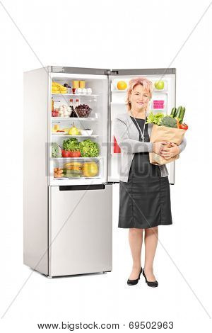 Full length portrait of a woman with bag of groceries in front of a fridge isolated on white background