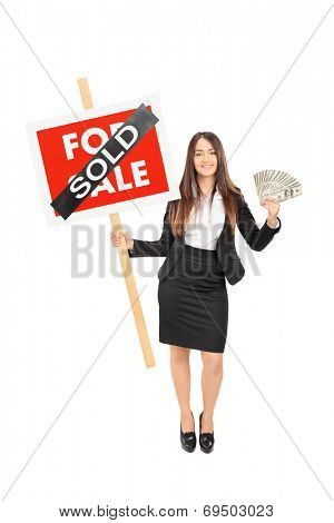 Full length portrait of a female realtor holding a sold sign an money isolated on white background
