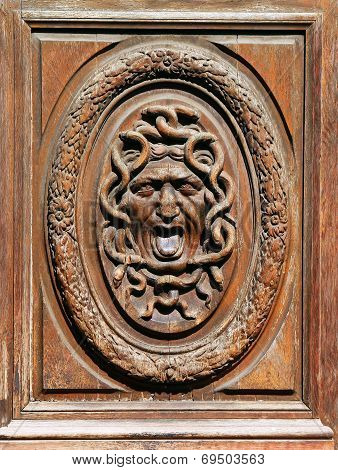Human Face Wrapped Up By Snakes In A Circular Frame On An Old Wooden Door. Photographed By The Passe