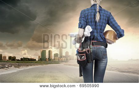 Bottom view of woman engineer with tool belt on waist