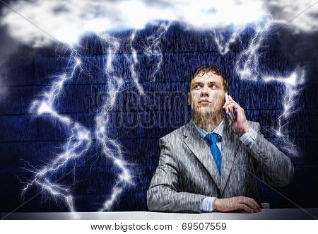 Young frustrated businessman under rain talking on mobile phone
