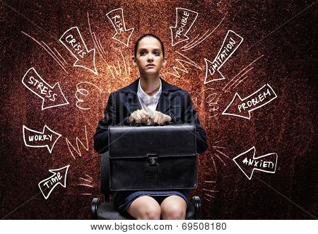 Young upset businesswoman sitting on chair with briefcase in hands