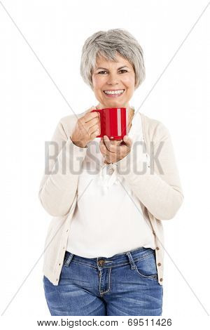 Happy elderly woman holding and drinking a cup of coffee