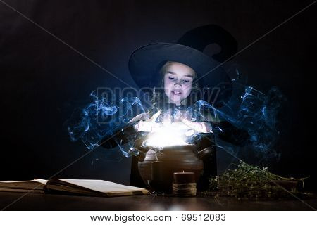 Little Halloween witch reading conjure above pot