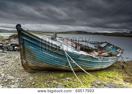 Weathered fishing boat lying on a rocky beach on the Isle of Lewis, Outer Hebrides, Scotland