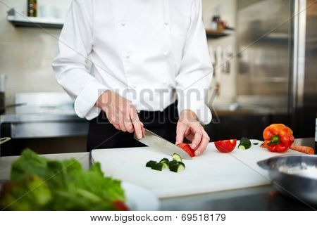 Image of male hand with knife cutting cucumber and tomato on wooden board