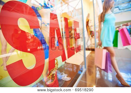 Word �¢??sale�¢?? on shop window with young shopper with paperbags on background