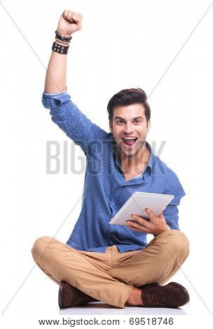 seated man celebrating success while working on tablet pad computer