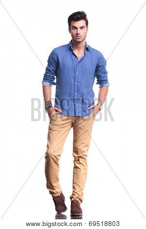 full body picture of a young casual man with hands in his pockets on white background